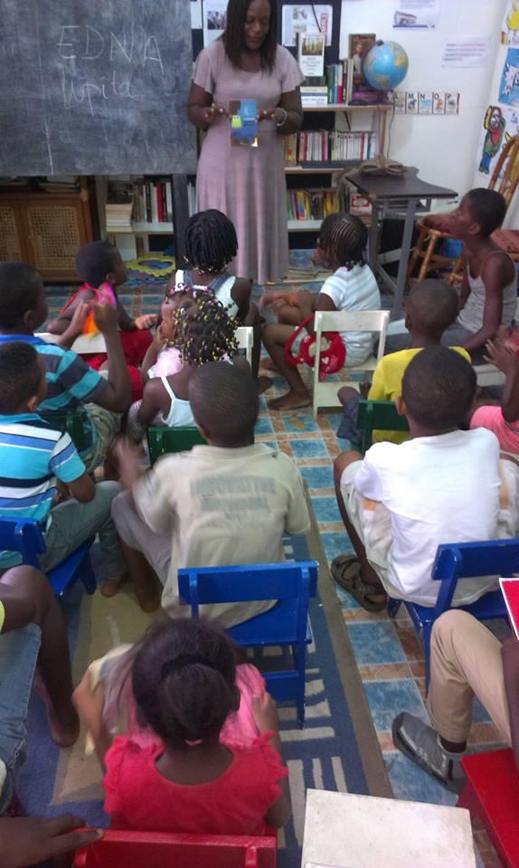 Edna avec des enfants montrant un livre